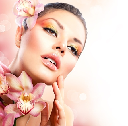 Photo pour Beautiful Spa Girl With Orchid Flowers Touching her Face  - image libre de droit
