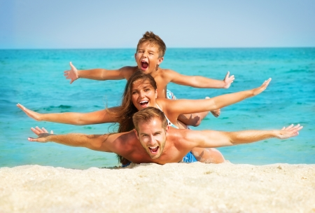 Foto de Happy Young Family with Little Kid Having Fun at the Beach  - Imagen libre de derechos