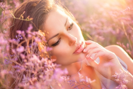 Foto de Beauty Girl Lying on a Meadow with Violet Flowers - Imagen libre de derechos