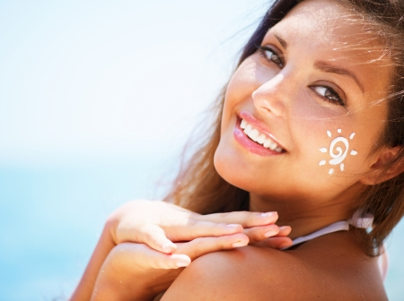Photo for Beautiful happy Girl applying Sun Tan Cream on her Face - Royalty Free Image