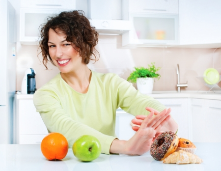 Dieting concept  Young Woman choosing between Fruits and Sweets