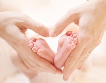 Photo pour Tiny Newborn Baby s feet on female Heart Shaped hands closeup - image libre de droit