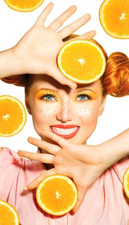 Beauty model girl takes juicy oranges  Freckles