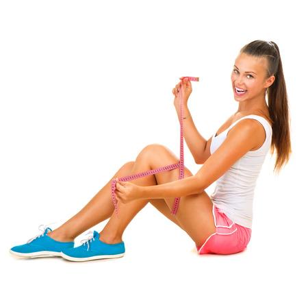 Photo pour Sporty model girl measures her leg with a measuring tape - image libre de droit