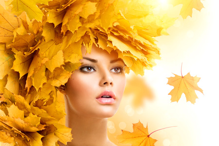 Autumn woman with yellow leaves hairstyle. Fall. Creative makeupの写真素材