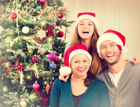 Foto de Christmas Family Portrait. Smiling Parents with Teenage Daughter - Imagen libre de derechos