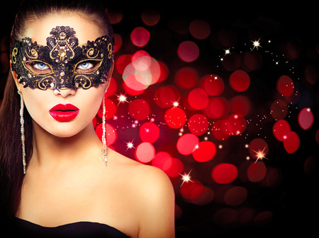 Photo for Woman wearing carnival mask over glowing red background - Royalty Free Image