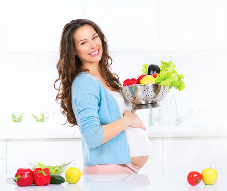 Foto de Pregnant young woman cooking vegetables. Healthy food - Imagen libre de derechos