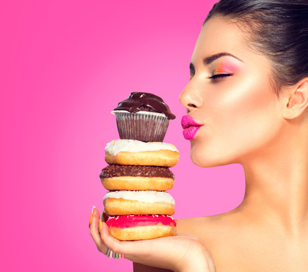 Beauty fashion model girl taking sweets and colorful donuts