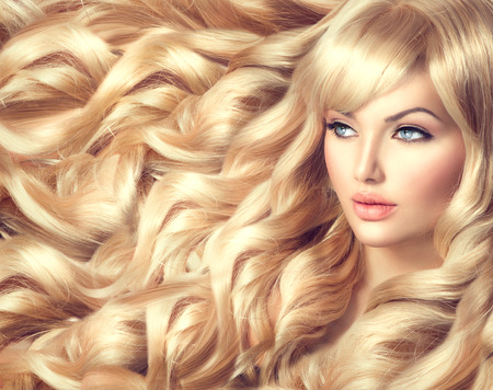 Beautiful model girl with long curly blond hairの写真素材