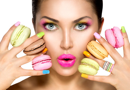 Beauty fashion model girl taking colorful macaroonsの写真素材