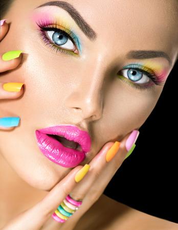 Photo pour Beauty girl face with vivid makeup and colorful nail polish - image libre de droit