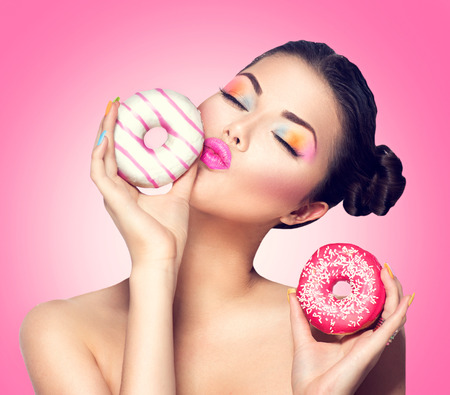 Foto de Beauty fashion model girl taking colorful donuts - Imagen libre de derechos