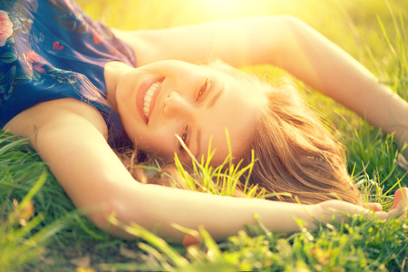 Beautiful young woman lying on the field in green grass