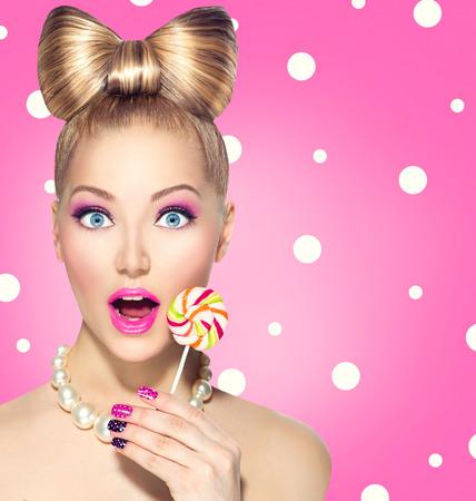 Funny girl eating lollipop over pink polka dots
