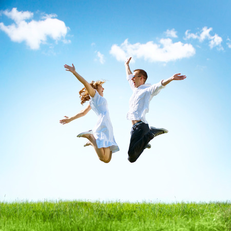 Photo pour Happy couple outdoor. Jumping family on green field - image libre de droit