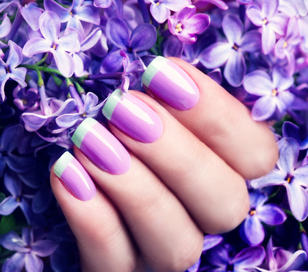 Manicured nails. Violet with green colors art manicure