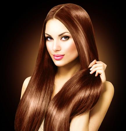 Beautiful brunette woman touching her long shiny straight hair