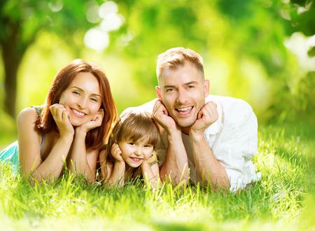 Foto de Happy joyful young family having fun in summer park - Imagen libre de derechos