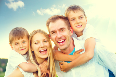 Happy joyful young family having fun in summer park