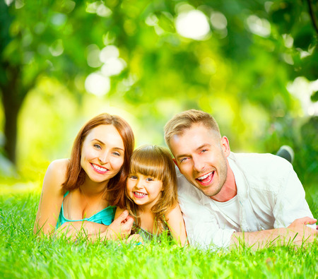 Foto de Happy joyful young family lying on green grass - Imagen libre de derechos