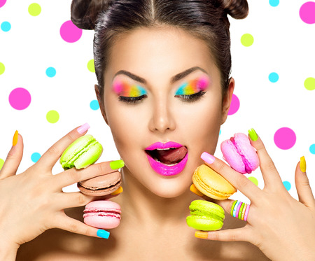 Photo pour Beauty fashion model girl with colourful makeup taking colorful macaroons - image libre de droit