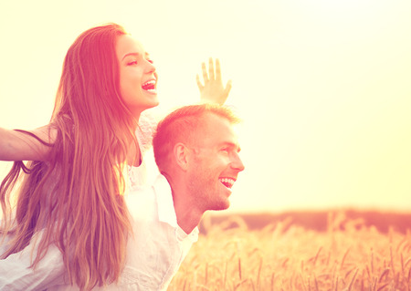 Happy couple having fun outdoors on wheat field over sunsetの写真素材