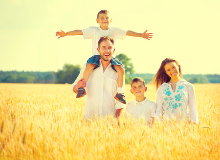 Happy young family on wheat summer field