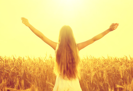 Photo for Beauty girl outdoors raising hands in sunlight rays - Royalty Free Image