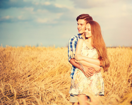 Foto de Happy couple kissing and hugging outdoors on wheat field, love concept - Imagen libre de derechos
