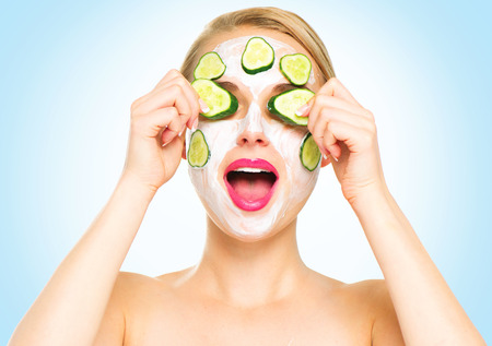 Photo for Funny spa woman applying fresh facial mask with cucumbers - Royalty Free Image