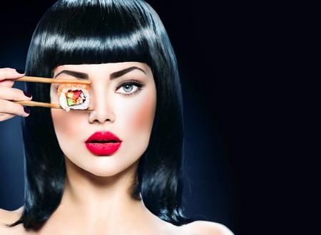 Photo pour Fashion art portrait of beauty model girl eating sushi roll - image libre de droit