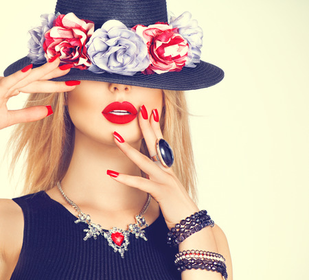 Beautiful sexy woman with red lips and manicure in modern black hatの写真素材