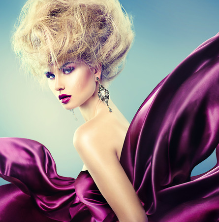 Photo for Glamor woman with updo hairstyle and bright makeup dressed in violet silk flying dress - Royalty Free Image