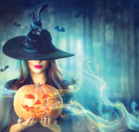 Halloween witch with a magic pumpkin in a dark forest