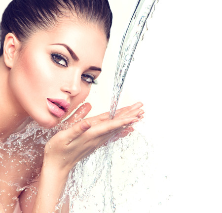 Foto de Beautiful model woman with splashes of water in her hands - Imagen libre de derechos