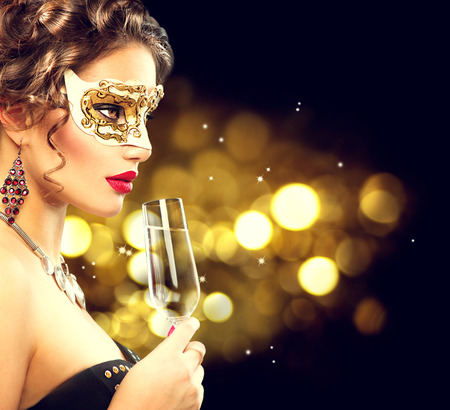 Sexy model woman with glass of champagne wearing venetian masquerade maskの写真素材