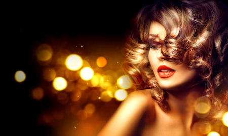 Beauty woman with beautiful makeup and curly hairstyle over holiday dark backgroundの写真素材