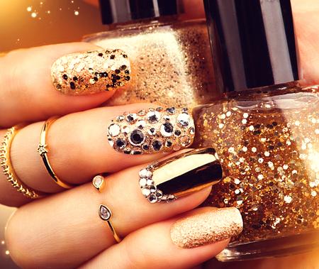 Foto de Golden holiday style bright manicure with gems and sparkles. Trendy accessories - Imagen libre de derechos