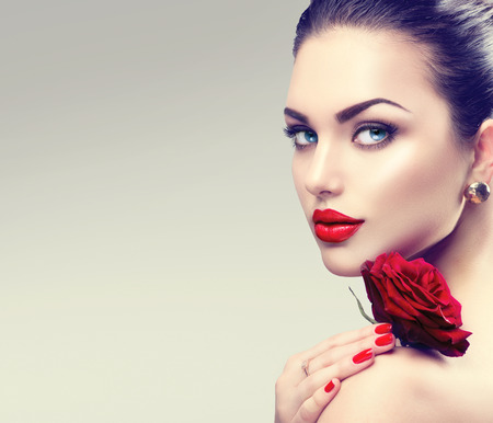 Foto de Beauty fashion model woman face. Portrait with red rose flower - Imagen libre de derechos