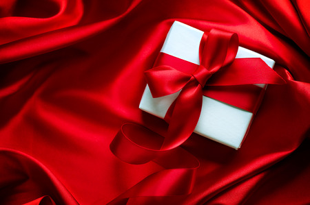 Photo for Valentine gift box with red satin ribbon on red silk background - Royalty Free Image