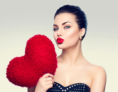 Photo for Gorgeous young brunette woman with heart shaped red pillow - Royalty Free Image