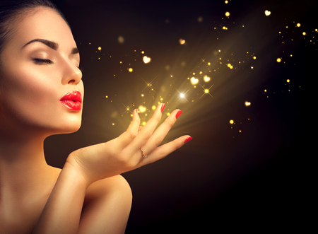 Photo pour Beauty young woman blowing magic dust with golden hearts - image libre de droit