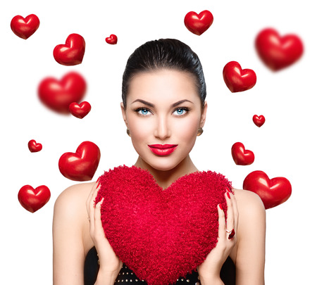 Photo pour Gorgeous young brunette woman with heart shaped red pillow. Perfect make up. Valentine' Day - image libre de droit