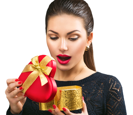 Beautiful surprised young woman opening heart shaped gift boxの写真素材