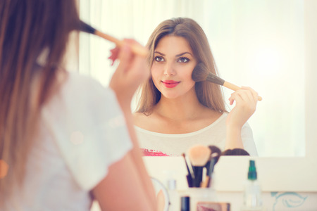 Foto de Beauty woman looking in the mirror and applying makeup - Imagen libre de derechos
