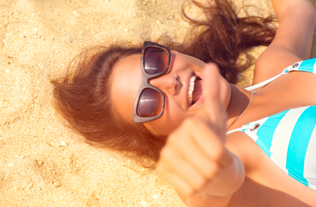 Happy beautiful model girl having fun on the beach. Summer vacation