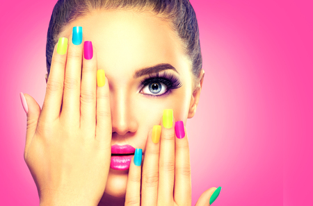 Beauty girl face with colorful nail polishの写真素材