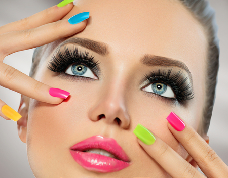 Beauty girl face with colorful nail polish. Manicure and makeupの写真素材