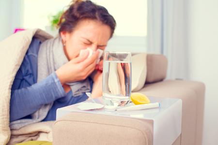 Foto de Sick woman sneezing into tissue. Flu. Woman caught cold - Imagen libre de derechos